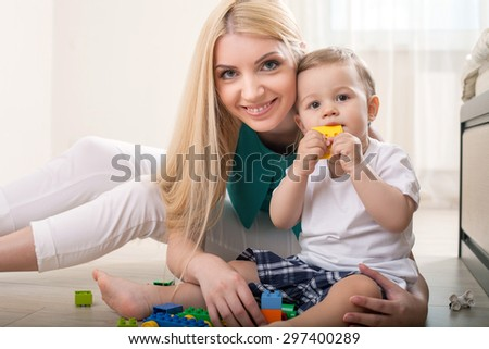 Pretty mother is sitting near her son and embracing him. They are looking at the camera with interest. The toddler is trying to bite the toy. His mamma is smiling - stock photo