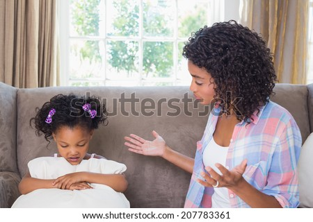 Pretty mother scolding her daughter on the couch at home in the living room - stock photo