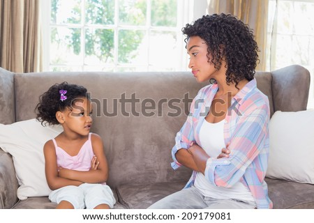Pretty mother sitting on couch with petulant daughter at home in the living room - stock photo