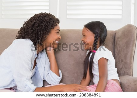 Pretty mother sitting on the couch with her daughter at home in the living room