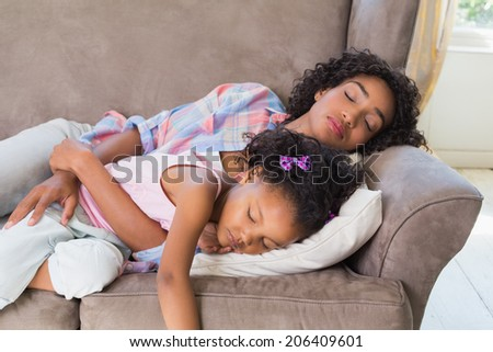Pretty mother sleeping with her daughter on the couch at home in the living room - stock photo
