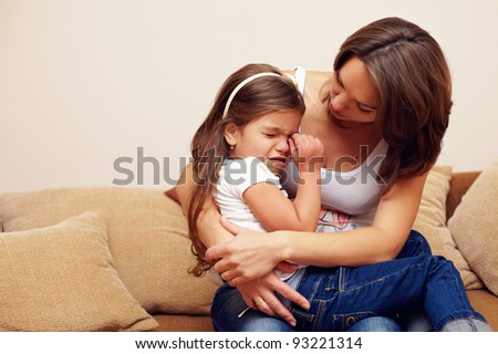 pretty mother soothing and hugging crying baby girl - stock photo