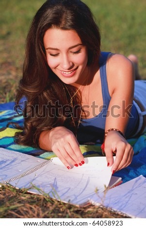 Pretty multicultural college teenager studying outdoors in a university campus. - stock photo