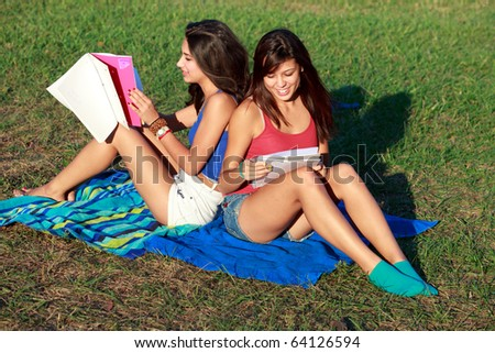 Pretty multicultural college teenagers studying outdoors on a university campus.