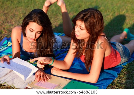 Pretty multicultural college teenagers studying outdoors on a university campus. - stock photo
