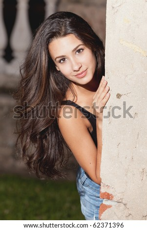 Pretty multicultural teenager in a lifestyle pose outdoors in the early evening. - stock photo