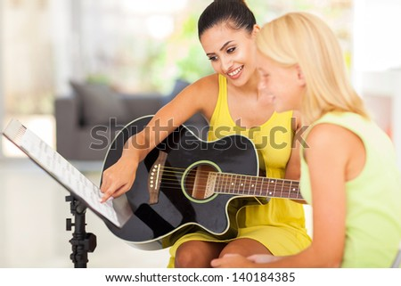 pretty music teacher tutoring young girl to play guitar - stock photo