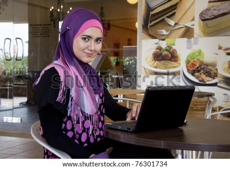 pretty muslim girl with laptop at cafe - stock photo