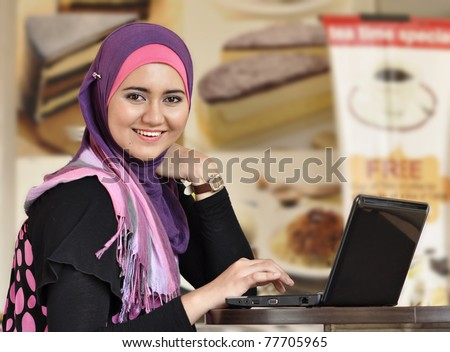 Pretty Muslim girl with laptop at cafe