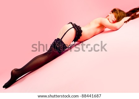 Pretty naked woman in stocking laying at pink background - stock photo