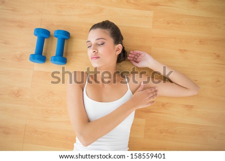 Pretty natural brown haired woman in white sportswear sleeping on the floor in bright living room - stock photo