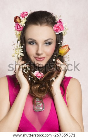 Pretty, natural, cheerful model with brown, curly hair with spring flowers. She wears pink dress with transparent part and nice silver necklace. - stock photo