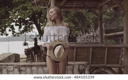 Pretty naturally looking woman on summer day in boho style fashion smiling while holding straw hat