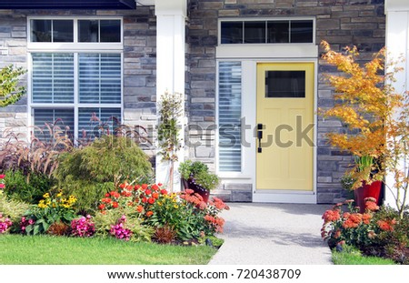 Pretty new home with a colorful front door and perennial garden.