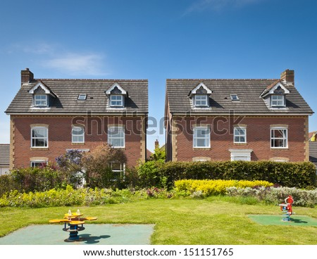 Pretty newly built homes and gardens against a clear blue summers sky. - stock photo