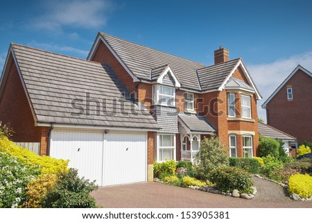 Pretty newly built homes and gardens against a clear blue summers sky. Stitched panoramic image detailed when viewed large. - stock photo