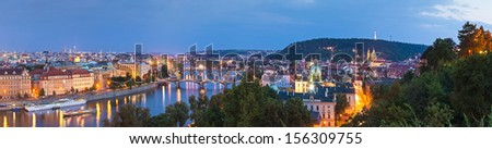 Pretty night time glow of the magical city of Prague reflected in the Vltava river, many sights visble including Charles bridge, Strakova Akademie and Church of Our Lady Tyn. - stock photo