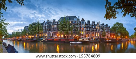 Pretty night time illuminations of dutch doll houses reflected in the tranquil canals of Amsterdam. - stock photo