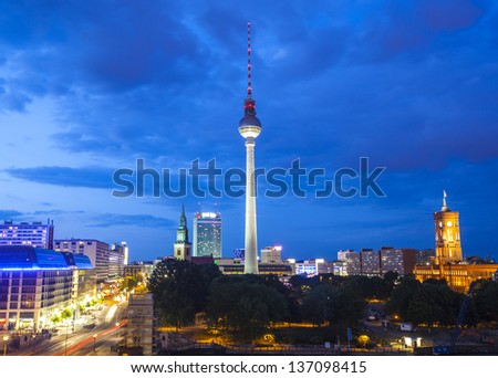 Pretty night time illuminations of the iconic Fernsehturm television tower overlooking Berlin cityscape from a dizzying 1200 ft in the Alexanderplatz district, many landmarks visible. - stock photo