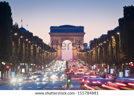 Pretty night time illuminations of the Impressive Arc de Triomphe (1833) along the famous tree lined Avenue des Champs-Elysees in Paris. - stock photo