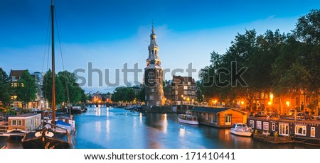 Pretty night time illuminations of the Montlebaanstoren Tower (1512) overlooking Oosterdk in central Amsterdam. - stock photo
