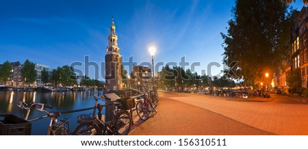Pretty night time illuminations of the Montlebaanstoren Tower (1512) overlooking Oosterdok and the ubiquitous dutch bicycles in central Amsterdam. - stock photo