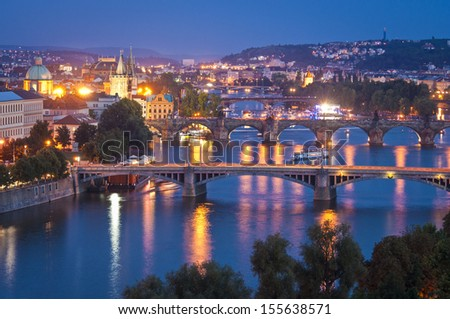 Pretty night time view of the magical Prague city reflected in the Vltava river, Charles bridge (1357) visible.