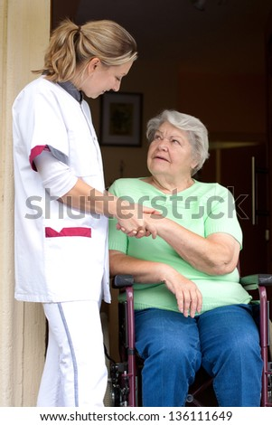 pretty Nurse and senior patient in a wheelchair gives each other a handshake - stock photo