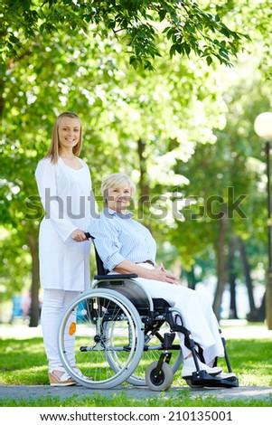 Pretty nurse and senior patient walking in park - stock photo