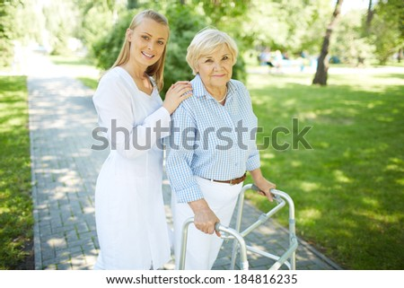 Pretty nurse and senior patient with walking frame looking at camera outside - stock photo