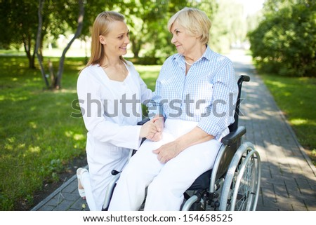 Pretty nurse talking to senior patient in a wheelchair in park - stock photo