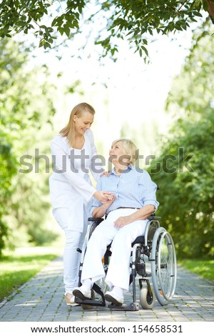 Pretty nurse walking with senior patient in a wheelchair in park - stock photo