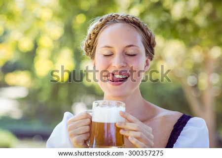Pretty oktoberfest blonde drinking in the park on a sunny day - stock photo