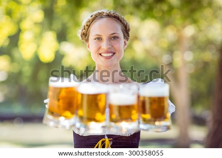 Pretty oktoberfest blonde holding beers on a sunny day - stock photo