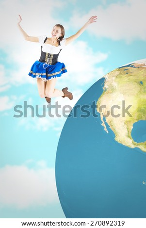 Pretty oktoberfest girl smiling and jumping against blue sky - stock photo