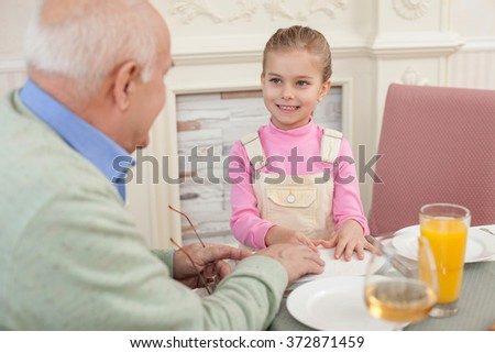 Pretty old man has a lunch with child - stock photo