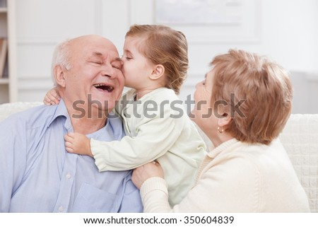 Pretty old men and women are spending time with their granddaughter. The girl is kissing her grandfather with joy. They are sitting on sofa and laughing - stock photo