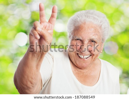 pretty old woman doing a victory gesture closeup - stock photo