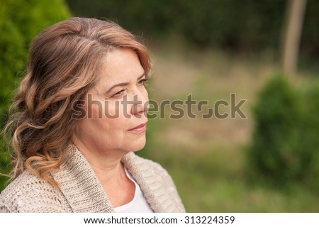 Pretty old woman is standing and resting in park. She is dreaming and looking aside pensively. Copy space in right side - stock photo
