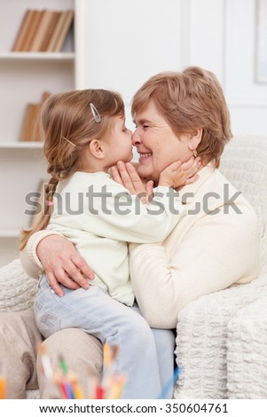 Pretty old woman is taking care of her granddaughter. She is sitting on sofa and holding a girl on her knees. They are embracing and laughing - stock photo