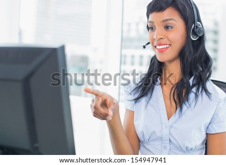 Pretty operator pointing her computer in office - stock photo
