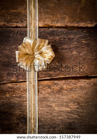 Pretty ornamental gold bow and ribbon over dark textured wooden planks with copyspace for your text or Christmas, anniversary or birthday greeting - stock photo