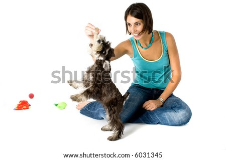 Pretty owner playing with her puppy - stock photo