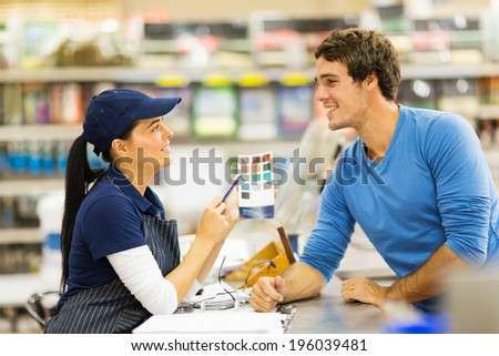 pretty paint store assistant helping customer choose paint color - stock photo