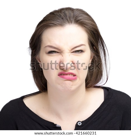Pretty pale woman with dark hair and green eyes. Isolated on a white background, looking at camera showing distaste.