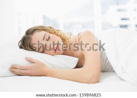 Pretty peaceful blonde lying in bed resting with closed eyes in bright bedroom - stock photo