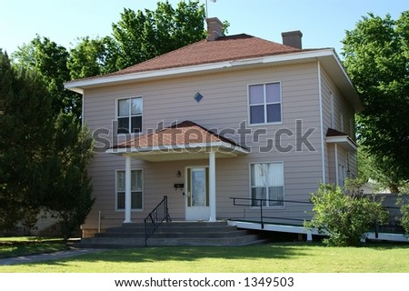 Pretty peach house with a simple, square design, small front porch, and a wheelchair ramp leading to the door from the side. - stock photo