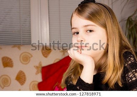 Pretty pensive little girl resting her chin on her hand and glancing sideways at the camera sitting indoors with copyspace - stock photo