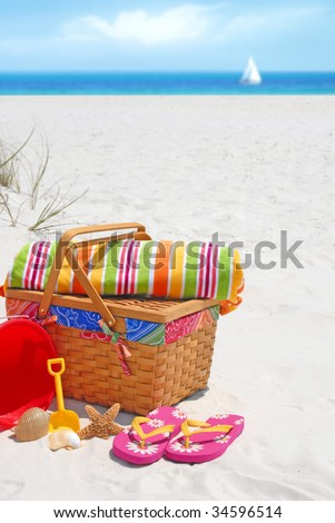Pretty picnic basket and beach supplies at seashore - stock photo