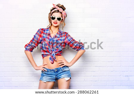 Pretty pin-up girl alluring by the brick wall in shorts and shirt. Beauty, fashion. Optics, eyewear. - stock photo